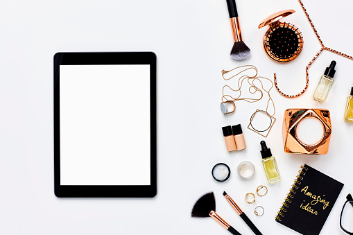 Directly above shot of digital tablet kept by beauty products