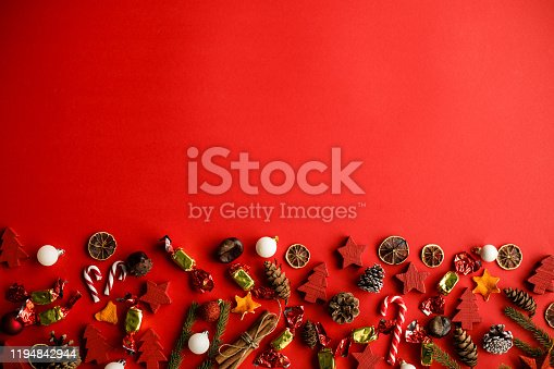 Copy space shot of bright red background with abundance of rustic looking candy, candy canes, pine cones, tree branches and Christmas ornaments.