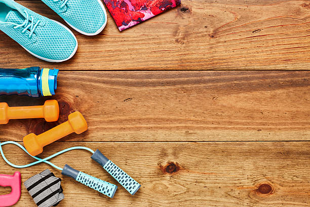 directly above shot of sports equipment on hardwood floor - exercise equipment stock photos and pictures