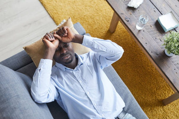 Directly above view of disturbed young Black man with closed eyes lying on psychiatrists couch and describing his feeling at therapy session stock photo