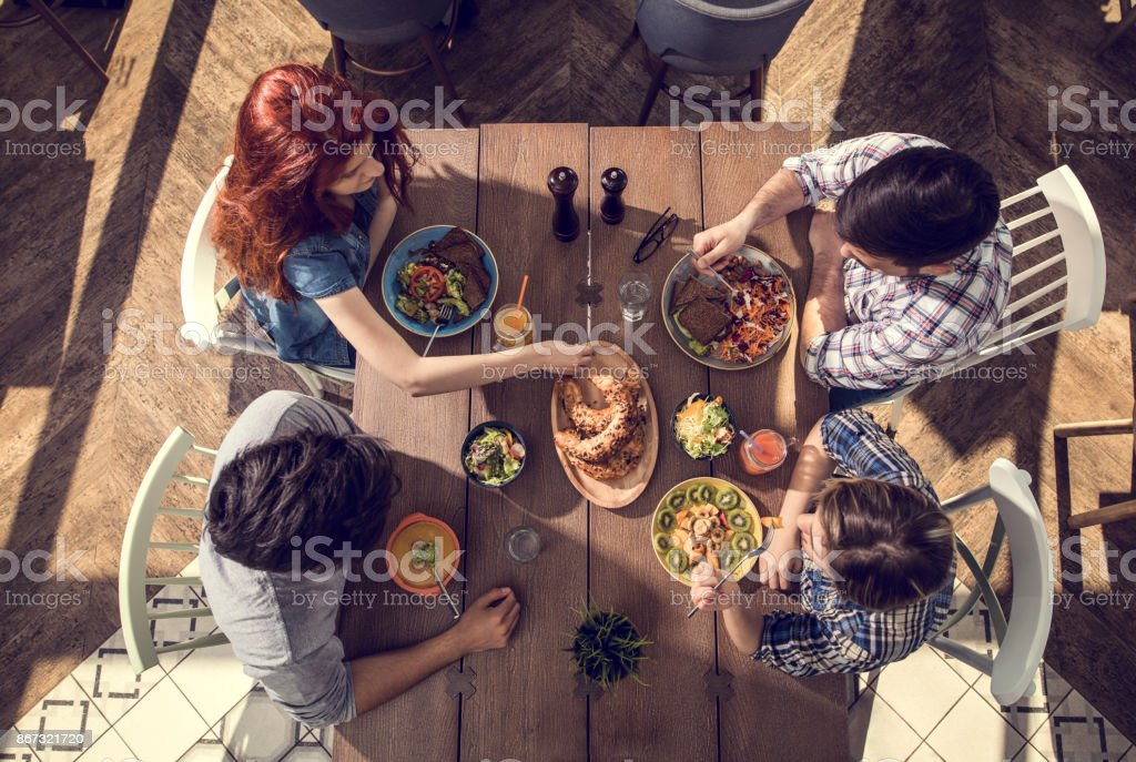 High angle view of young people enjoying in healthy meal at the...