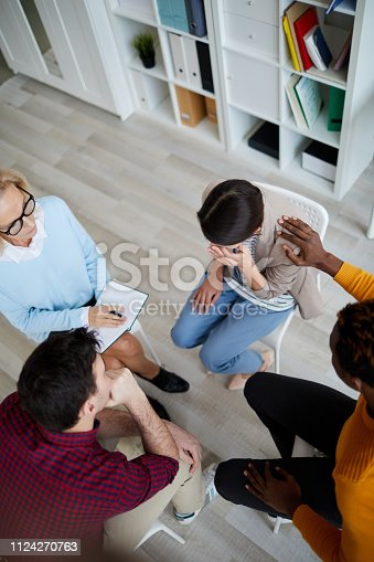 istock Directly above view of support group sitting in circle at therapy session and discussing problems of each other, black man consoling crying woman 1124270763