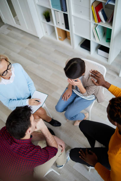 Directly above view of support group sitting in circle at therapy session and discussing problems of each other, black man consoling crying woman stock photo