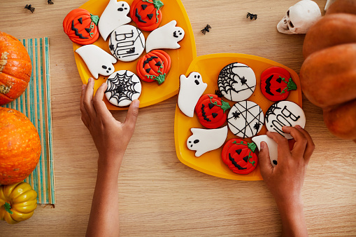 Directly above view of unrecognizable boy adjusting gingerbread cookies on plates while preparing sweets for Halloween party