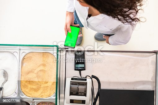 istock Directly above view of woman paying contactless 962077786
