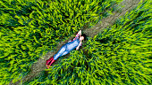 Directly above view of young farmer lying on wheat field