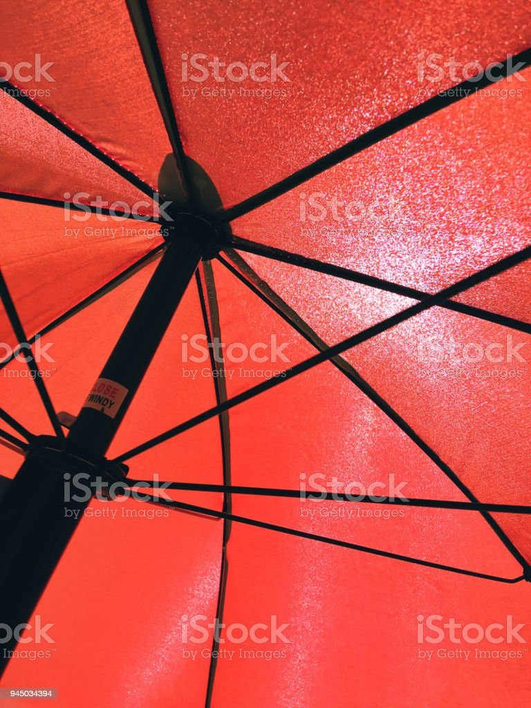 Directly below shot of red beach umbrella backlit by sun stock photo