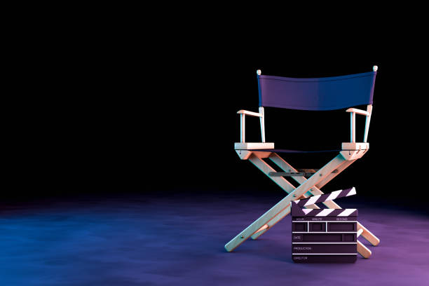 Director Chair and Movie Clapper with neon lights on black background stock photo