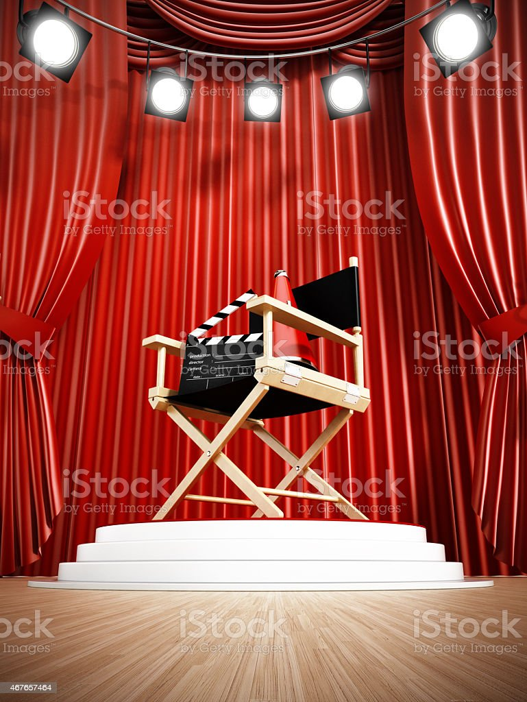 Spotlit director\'s chair on the stage against red curtains. There are...