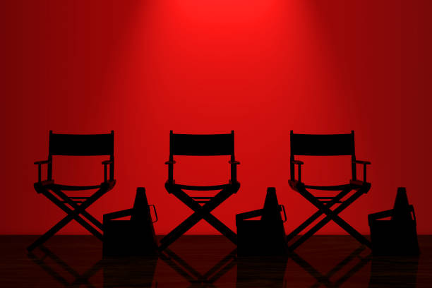 Director Chairs, Movie Clappers and Megaphones with Red Backlight in front of Wall. 3d Rendering stock photo