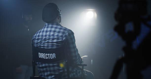 direktor, sitzt in seinem sessel auf einem filmset - geführtes lesen stock-fotos und bilder