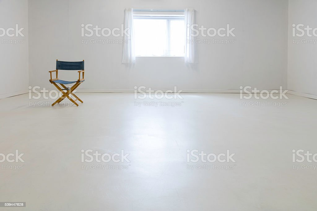 A chair sitting in a bare room with white floor, white walls and...