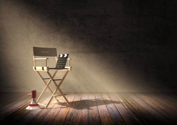 Director's chair with clapper board and megaphone in dark room stock photo