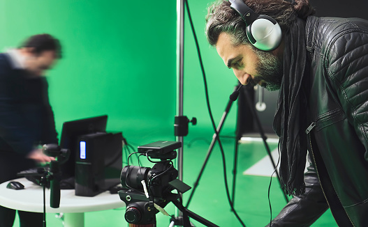 Camera operators working on backstage in green box studio