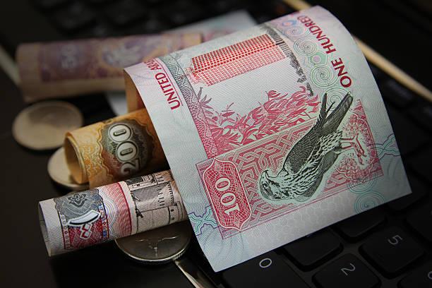 UAE Dirhams banknote on top keyboard stock photo