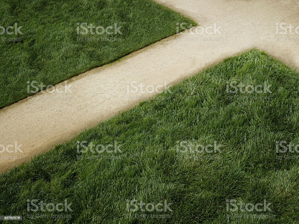 Dirt arrow surrounded by grass royalty-free stock photo