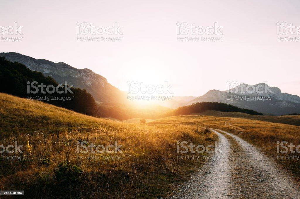 Dirt gravel mountain road on sunset. stock photo