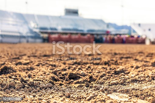 Close-up on rough soil the foreground, with the arena and stadium seating defocused in the distance.