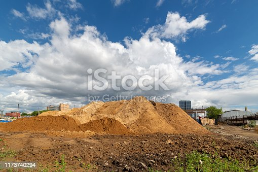 Dirt mound on a background of blue sky with white clouds.