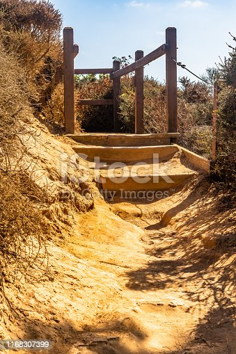 Dirt path through sandstone desert land on uphill mountain climb. Hike/ Hiking trail landscape in San Diego, southern California. Hot dry humid sunny summer day in La Jolla, Torrey Pines.