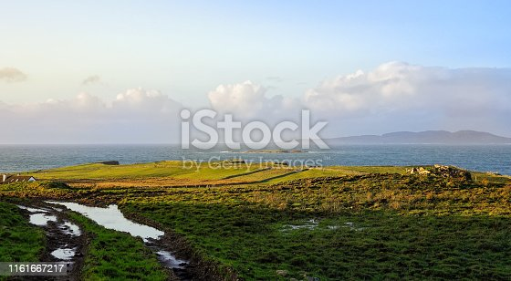 Dirt road and green fields on the coast, coastline and islands with mountains in a distance, moody blue sky with clouds, Wiled Atlantic Way, Ireland
