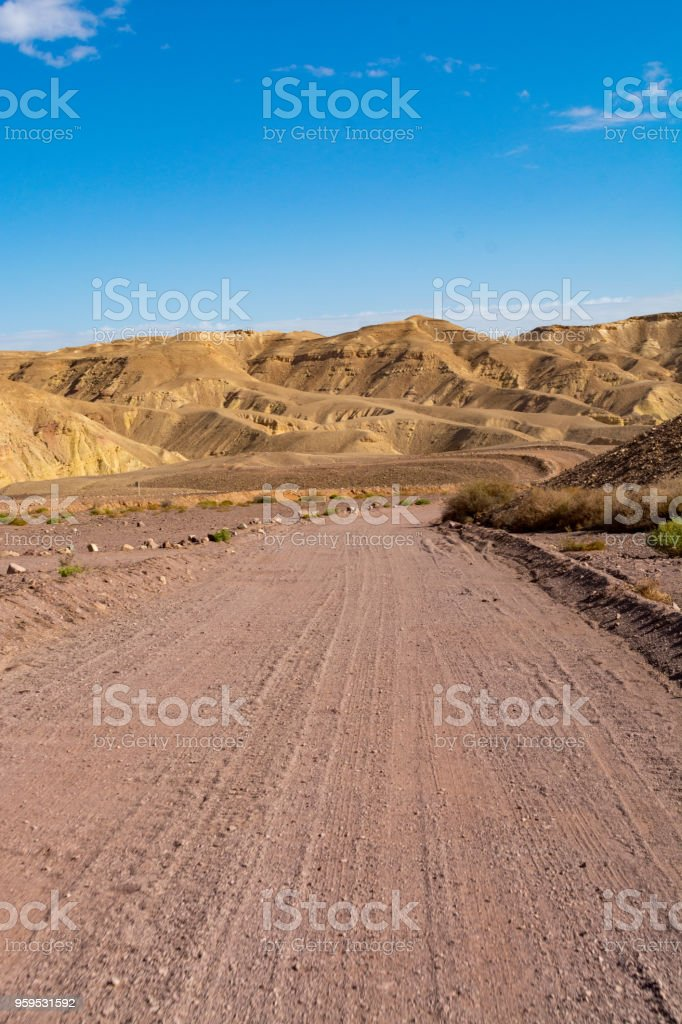 Dirt road in desert Negev, Israel,  transport infrastructure in desert, scenic mountains route from Eilat to north of Israel stock photo