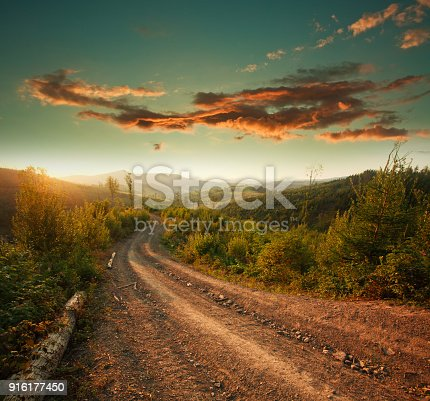 1155573645istockphoto Dirt road in mountains at sunset dramatic sky background 916177450