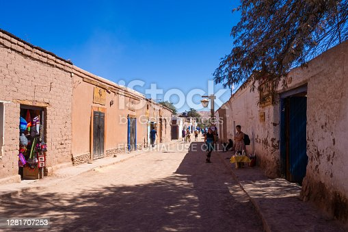 Dirt road in the center of San Pedro de Atacama, with a storefront in the foreground. Chile.