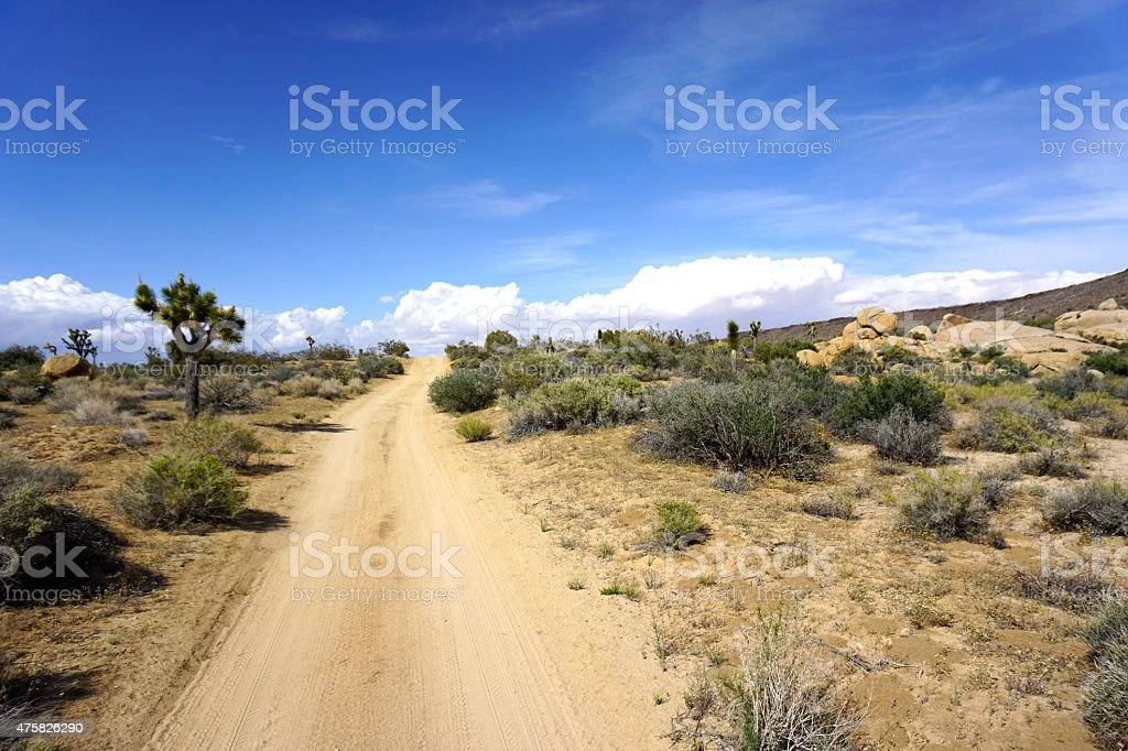Dirt road in the desert with clouds stock photo
