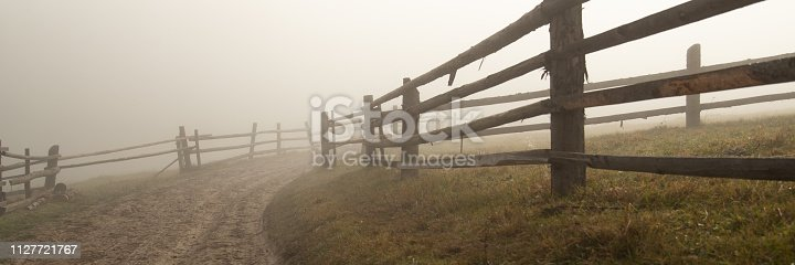 An old wooden fence along the mystical dirt road in the fog. Autumn concept. Mysticism.