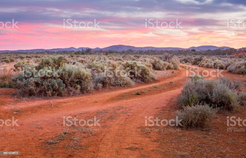 穿過沙漠平原通往山脈的土路 - 免版稅不毛之地圖庫照片