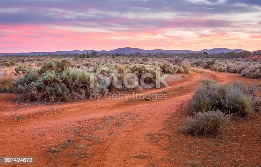 Dirt road leads through the saltbush plains to the ranges  in outback Australia