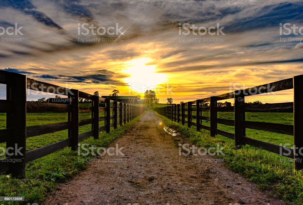 Dirt road  leading to a barn with sunset stock photo
