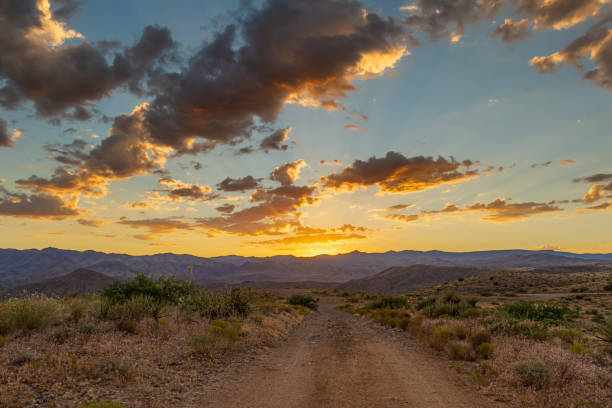 A dirt road leading to distant mountains where the sun has just set behind with colorful clouds stock photo