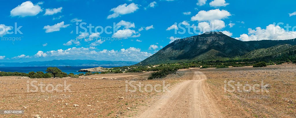 dirt road leading to mountains stock photo