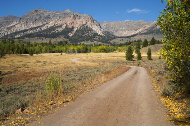 A dirt road leads to mountains on a sunny autumn afternoon. stock photo