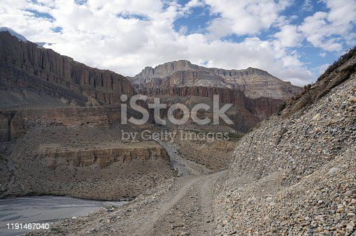 A dirt road leads to Upper Mustang along the banks of the Kali Gandaki River among the Himalayan Mountains in Nepal.