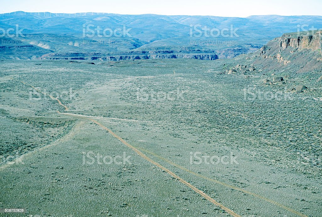 Dirt road on valley floor to gorge below wind farm stock photo