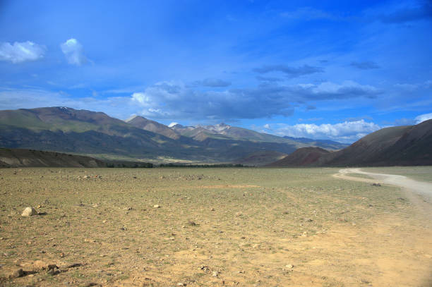 A dirt road running through the steppe surrounded by high mountains. A dirt road running through the steppe surrounded by high mountains. Kurai steppe, Altai, Russia. steppe stock pictures, royalty-free photos & images