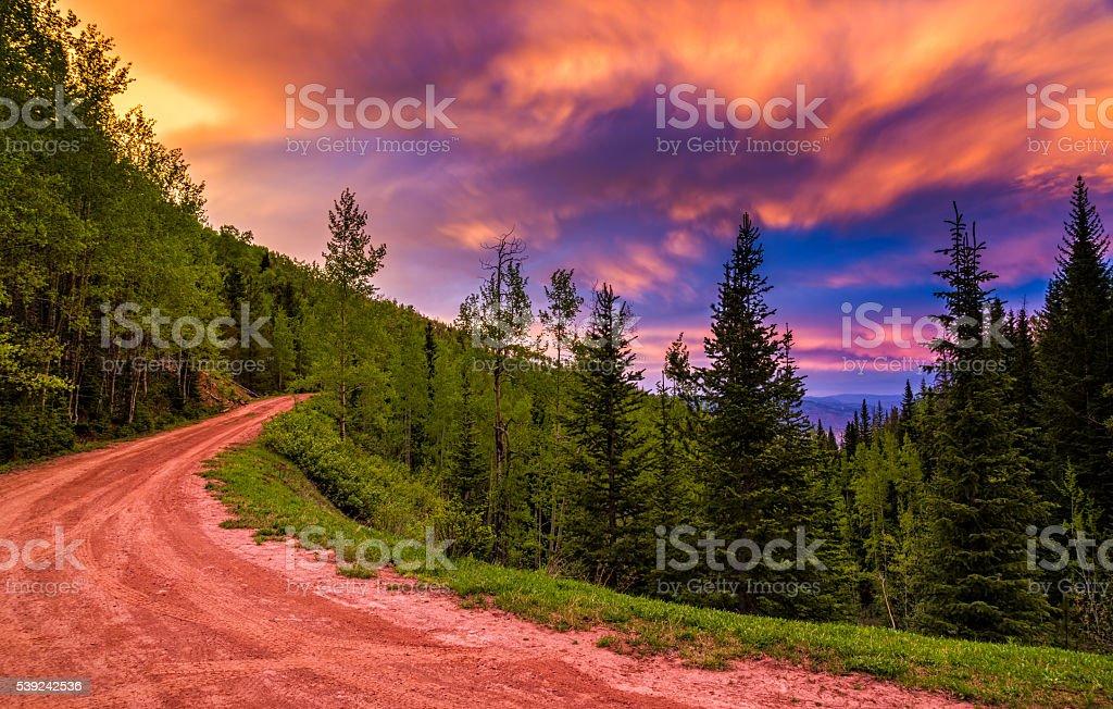 Carretera de tierra atardecer con vista a las montañas y una colorida nubes foto de stock libre de derechos