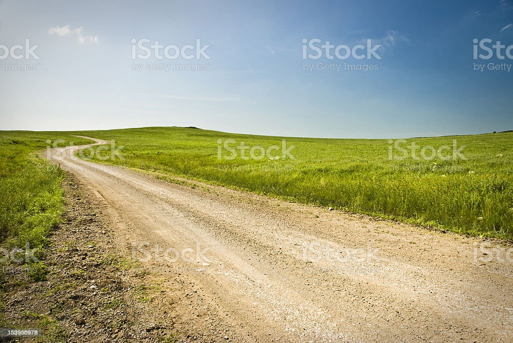Dirt road through the prairie stock photo