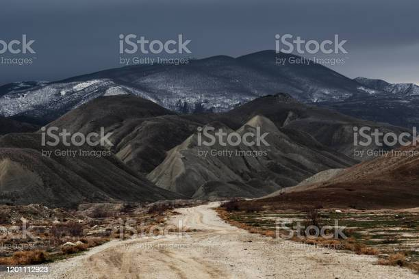 Photo of Dirt road to the mountains at stormy weather
