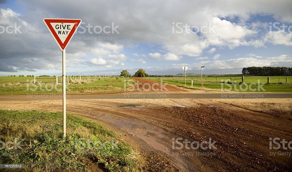 A dirt road with a sign that states give way stock photo
