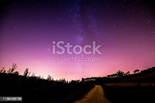 A quiet country side short cut road leads to a purple-pink sky filled with stars and the milky way in Portugal.