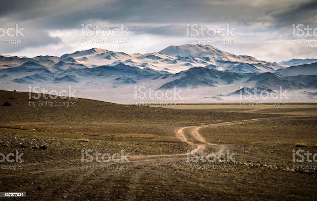 Dirt roadway towards vast mountain landscape stock photo