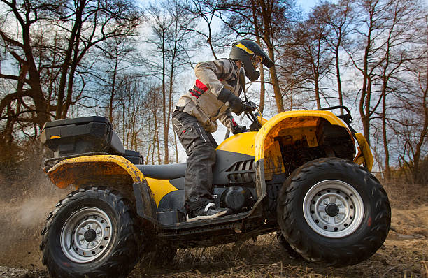 Dirt spinning of the ATV quad bike wheels Horizontal motion portrait of a man in gray sport jacket and safety helmet and goggles driving mud-covered yellow ATV 4x4 quad bike with dirt spinning of the wheels. quadbike stock pictures, royalty-free photos & images