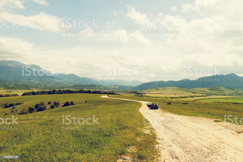 Dirt track road with car in Carpathian Mountain Range Romania stock photo