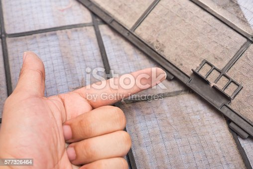 istock dirty air conditioner filter and dirty finger 577326464