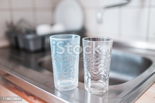 istock Dirty and clean glass cups on a kitchen sink. Broken washing machine concept. 1139229542
