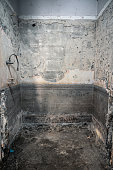 Dirty bathroom removal of tile with demolition and renovation